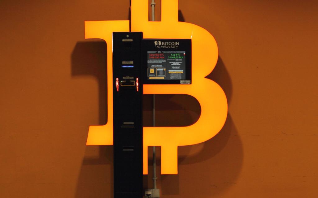 Bitcoin automat umístěný uprostřed znaku Bitcoinu.